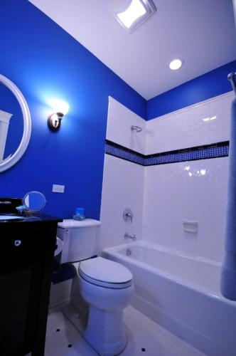 A bright blue bathroom with white tile, tub and toilet.